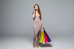 Young woman using cellphone while carrying shopping bag on grey background Stock Photos