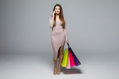 Young woman using cellphone while carrying shopping bag on grey background Royalty Free Stock Photos
