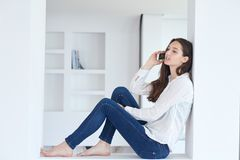 Young woman using cellphone at home Royalty Free Stock Image