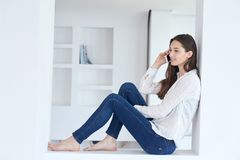 Young woman using cellphone at home Royalty Free Stock Photos