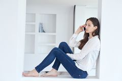 Young woman using cellphone at home Royalty Free Stock Photo