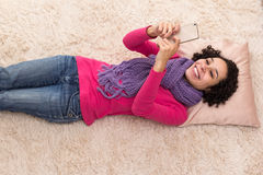 Young woman is using cellphone. Lying on the rug. Stock Image