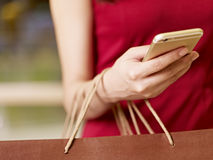 Young woman using cellphone while shopping Stock Photo