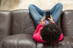 Young woman using cellphone, sitting in a brown couch. Royalty Free Stock Photo