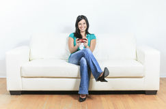 Young woman using a cellphone on the sofa Stock Photos