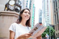 Young woman using city guide in Hong Kong Stock Photo