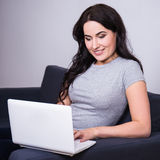 Young woman using computer at home Stock Image
