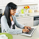 Young woman using computer in kitchen. Smiling black woman using computer in modern kitchen interior Stock Photos