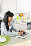 Young woman using computer in kitchen Royalty Free Stock Photography