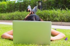 Young woman using computer laptop and laying on the grass garden. Computer and outdoor concept Royalty Free Stock Images