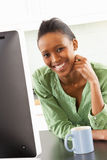 Young Woman Using Computer In Modern Kitchen Royalty Free Stock Image