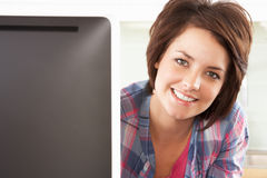 Young Woman Using Computer In Modern Kitchen. Smiling At Camera Stock Image