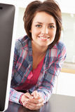 Young Woman Using Computer In Modern Kitchen. Smiling At Camera Royalty Free Stock Image