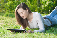 Young woman using computer tablet pc outdoor in the park Royalty Free Stock Photos
