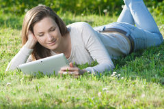 Young woman using computer tablet pc outdoor in the park Royalty Free Stock Images