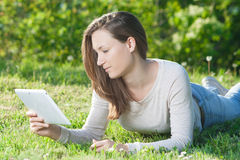 Young woman using computer tablet pc outdoor in the park Stock Images