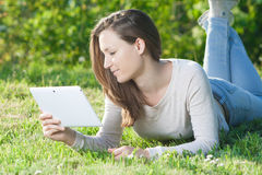 Young woman using computer tablet pc outdoor in the park Royalty Free Stock Image