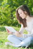 Young woman using computer tablet pc outdoor in the park Stock Photos