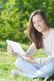 Young woman using computer tablet pc outdoor in the park Stock Photography
