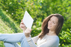 Young woman using computer tablet pc outdoor in the park Royalty Free Stock Photography