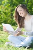 Young woman using computer tablet pc outdoor in the park Stock Photo
