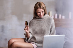 Young woman using credit card and laptop Stock Images