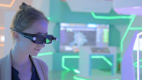 Young woman using 3d augmented reality glasses. With motion sensor at technology exhibition. Futuristic background. Future and interactive concept stock video footage