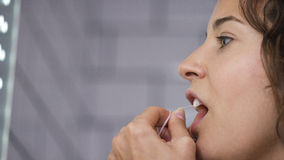 Young woman using dental floss in the bathroom Stock Image
