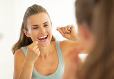 Young woman using dental floss in bathroom Stock Photos