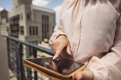 Young woman using digital tablet on balcony Stock Photos