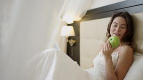 Young woman using digital tablet on bed with an appla in her hand. Young cheerful woman dressed in sleepwear is using digital tablet on bed with an appla in her stock video footage