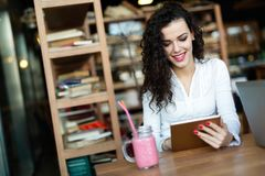Young woman using digital tablet in coffee shop. Young attractive woman using digital tablet in coffee shop Royalty Free Stock Images