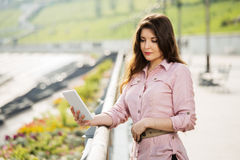 Young fashion woman using tablet computer outdoor Royalty Free Stock Image