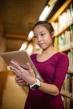 Young woman using digital tablet in library Royalty Free Stock Photography