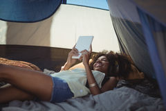 Young woman using digital tablet while lying down in tent Royalty Free Stock Image