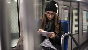 Young woman using digital tablet in metro royalty free stock photos