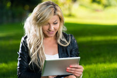 Young Woman using a digital tablet in the park. Woman Lying On Grass With Digital Tablet Stock Images