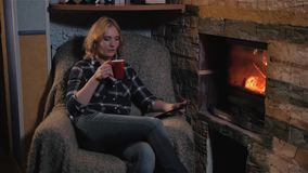 Young Woman Using Digital Tablet PC And Enjoying Winter Hot Drink Sitting By Fireplace at Home stock video