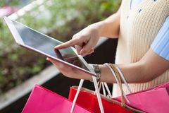 Young woman using digital tablet shoopping online with many colo Stock Photos