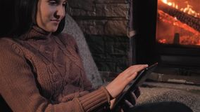 Young Woman Using Digital Tablet Sitting By Fireplace at Home, Close Up Shot stock video