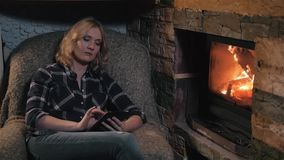 Young Woman Using Digital Tablet Sitting By Fireplace at Home stock video footage