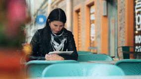 Young woman using digital tablet at street cafe stock footage