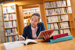 Young woman using digital tablet while studying in library Stock Photo