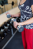 Young woman using dumbbells in a gym Stock Photo