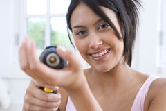 Young woman using electric drill, smiling, portrait (differential focus) Stock Photo
