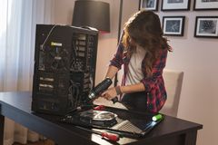 Young woman using electrical screwdriver to fix a computer royalty free stock image
