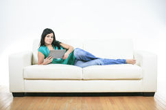 Young woman using electronic tablet sitting on Royalty Free Stock Photo