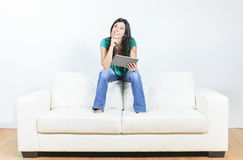 Young woman using electronic tablet sitting on Stock Photos