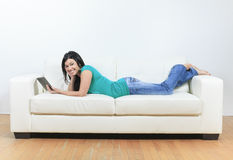 Young woman using electronic tablet sitting on Stock Images