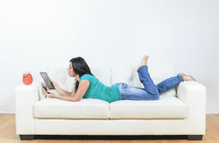 Young woman using electronic tablet sitting on Royalty Free Stock Image